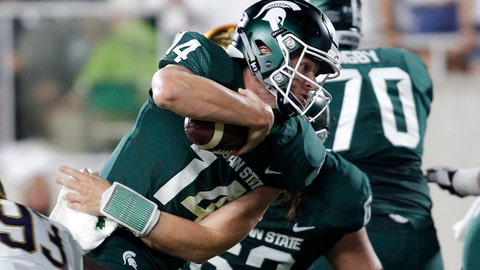 Michigan State quarterback Brian Lewerke (14) runs for a first down as Notre Dame's Jay Hayes (93) defends during the first quarter of an NCAA college football game, Saturday, Sept. 23, 2017, in East Lansing, Mich. (AP Photo/Al Goldis)