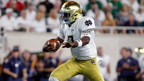 Notre Dame quarterback Brandon Wimbush runs for a 16-yard touchdown as Michigan State's Mike Panasiuk, bottom right, and Raequan Williams watch during the first quarter of an NCAA college football game, Saturday, Sept. 23, 2017, in East Lansing, Mich. (AP Photo/Al Goldis)