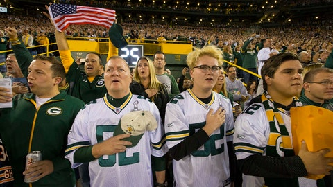 Sep 28, 2017; Green Bay, WI, USA; Scott Sheffield (second from left) and his sons, Connor and Spencer, stand for the national anthem before the Green Bay Packers game against the Chicago Bears at Lambeau Field. The family from St. George, Utah, said they weren't going to lock arms because it seemed more like an anti-President Trump protest. To demonstrate unity, Green Bay Packers quarterback Aaron Rodgers requested that  fans to join players, locking arms in the stands during the national anthem. Some fans are angry at the team and players for what they perceive as showing disrespect for the nation, the flag, the military or the national anthem by sitting, kneeling, remaining in the locker room or locking arms during the national anthem. Supporters say players are peacefully exercising their free speech rights on the best stage available. Mandatory Credit: Mark Hoffman/Milwaukee Journal Sentinel via USA TODAY Sports