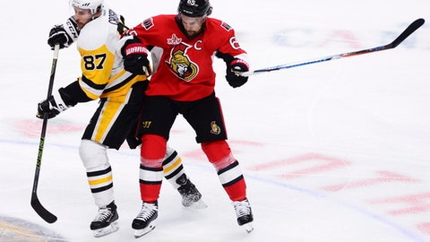 Pittsburgh Penguins centre Sidney Crosby (87) and Ottawa Senators defenseman Erik Karlsson (65) collide during the second period of game six of the Eastern Conference final in the NHL Stanley Cup hockey playoffs in Ottawa on Tuesday, May 23, 2017. (Sean Kilpatrick/The Canadian Press via AP)