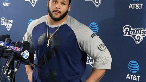 FILE - In this April 10, 2017, file photo, Los Angeles Rams defensive lineman Aaron Donald speaks with reporters after the first official day of the team's offseason football training program in Thousand Oaks, Calif. Donald has not reported to the Rams' training camp, and general manager Les Snead says the club will continue negotiations on a contract extension. Donald didn't join his veteran teammates in reporting to UC Irvine on Friday, July 28. The fourth-year pro also skipped several weeks of offseason workouts while his agent worked on a new deal that will make him one of the highest-paid players in the NFL. (AP Photo/Greg Beacham, file)