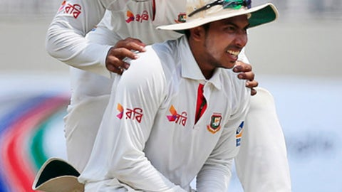 Bangladesh's Imrul Kayes congratulates his teammate Soumya Sarkar, on ground, for taking a catch to successfully dismiss Australia's Peter Handscomb, unseen, during the fourth day of their first test cricket match in Dhaka, Bangladesh, Wednesday, Aug. 30, 2017. (AP Photo/A.M. Ahad)