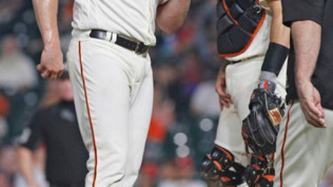 San Francisco Giants pitcher Mark Melancon, left, chats with Buster Posey, center, as Giants manager Bruce Bochy, right, approaches to take Melancon out of the baseball game against the St. Louis Cardinals, during the eighth inning Thursday, Aug. 31, 2017, in San Francisco. (AP Photo/George Nikitin)
