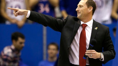 FILE - In this Dec. 5, 2014, file photo, Kansas NCAA college football coach David Beaty points to the crowd during halftime of an NCAA college basketball game against Florida, in Lawrence, Kan. What can ultimately set schools apart are the small touches _ the way a coach rewards a walk-on, for instance. There's a feeling of authenticity to those behind-the-scenes moments, almost as if social media can pull back the curtain on the inner-workings of a program. (AP Photo/Orlin Wagner, File)