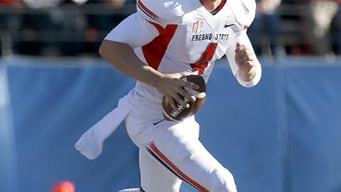 FILE - In this Nov. 29, 2013, file photo, Fresno State quarterback Derek Carr runs with the ball against San Jose State during an NCAA college football game in San Jose, Calif. Carr will take a short break from preparations for the start of the season for the Oakland Raiders to receive an honor he's dreamed about for years. Carr will go back to Fresno State on Saturday night to have his No. 4 jersey retired in a ceremony at halftime of the Bulldogs' season opener against Incarnate Ward. (AP Photo/Tony Avelar, File)