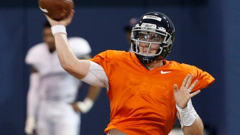 FILE - This Thursday April 6, 2017, file photo shows Virginia quarterback Kurt Benkert throwing a pass during a spring football practice at their indoor facility in Charlottesville, Va. A lingering shadow still looms over Virginia following the tragedy that hit the campus and Charlottesville community three weeks ago. So the university is using sports to promote inclusion, and the effort begins Saturday when Virginia plays host to William & Mary in the season-opener for both football programs.  Benkert knows the easiest way for he and his teammates to do their part: win the game. (AP Photo/Steve Helber, File)