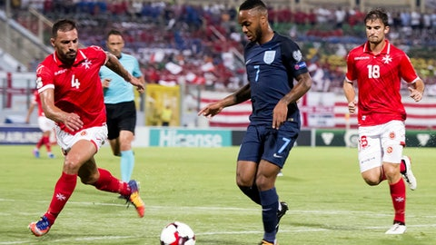 England's Raheem Sterling, center, is challenged by Malta's Steve Borg, left, during the World Cup group F qualifying soccer match between Malta and England, at the Ta Qali stadium, in Valletta, Malta, Friday Sept.1, 2017. (AP Photo/Rene Rossignaud)