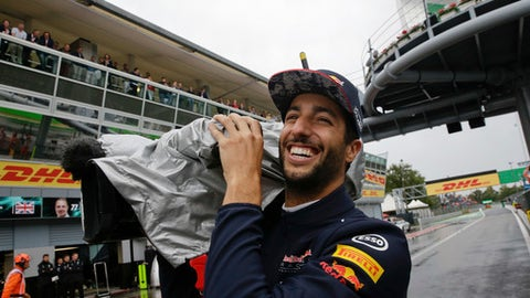 Red Bull driver Daniel Ricciardo of Australia plays with a camera during a stop due to heavy rain in the qualifying session at the Monza racetrack, in Monza, Italy, Saturday, Sept. 2, 2017. The Italian Formula one GP race will be held on Sunday. (AP Photo/Luca Bruno, Pool)