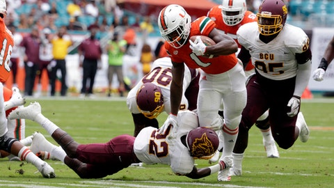 Miami running back Mark Walton (1) runs as Bethune-Cookman safety Diquan Richardson (22) attempts a tackle during the first half of an NCAA college football game, Saturday, Sept. 2, 2017, in Miami Gardens, Fla. (AP Photo/Lynne Sladky)