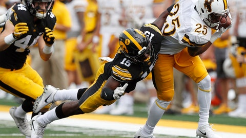 Wyoming wide receiver Austin Conway (25) is tackled by Iowa defensive back Joshua Jackson (15) after making a reception during the first half of an NCAA college football game, Saturday, Sept. 2, 2017, in Iowa City, Iowa. Iowa won 24-3. (AP Photo/Charlie Neibergall)