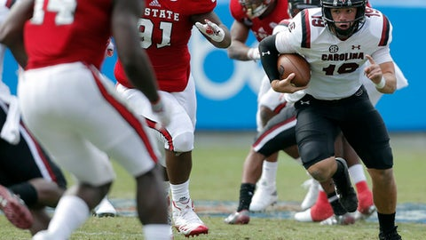 South Carolina's Jake Bentley (19) keeps his head low as he rushes for a first down, chased by North Carolina State's Eurndraus Bryant (91) and other defensive players during the first half of a college football game in Charlotte, N.C., Saturday, Sept. 2, 2017. (AP Photo/Bob Leverone)