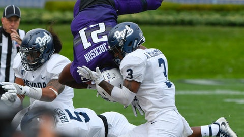 Northwestern defensive back Alonzo Mayo (12) gets flipped in the air by Nevada linebacker Gabriel Sewell, left, Nevada defensive back Dameon Baber (5) and Nevada defensive back Ahki Muhammad (3) during the first half of an NCAA college football game in Evanston, Ill., Saturday, Sept. 2, 2017. (AP Photo/Matt Marton)