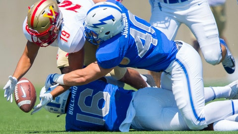 VMI defensive back Isaiah Parker (19)  dives for the ball against Air Force defenders Kyle Johnson and Robert Bullard during an NCAA college football game in Colorado Springs, Colo., Saturday, Sept. 2, 2017. (Dougal Brownlie/The Gazette via AP)