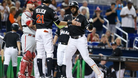 Miami Marlins' Marcell Ozuna, right, celebrates with Christian Yelich, left, after Ozuna hit a home run scoring Yelich during the first inning of a baseball game against the Philadelphia Phillies, Saturday, Sept. 2, 2017, in Miami. (AP Photo/Wilfredo Lee)