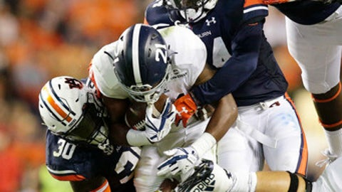 Georgia Southern running back Wesley Fields is tackled by Auburn linebacker Tre' Williams, bottom, linebacker Jeff Holland, and defensive lineman Marlon Davidson, top in the first half of an NCAA college football game, Saturday, Sept. 2, 2017, in Auburn, Ala. (AP Photo/Brynn Anderson)
