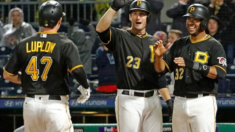 Pittsburgh Pirates' Jordan Luplow (47) is greeted by David Freese (23) and Elias Diaz (32) who were on base for his three-run home run off Cincinnati Reds relief pitcher Wandy Peralta during the eighth inning of a baseball game in Pittsburgh, Saturday, Sept. 2, 2017. The Pirates won 5-0. (AP Photo/Gene J. Puskar)
