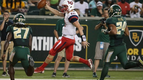 Liberty quarterback Stephen Calvert, center, scores past Baylor cornerback Verkedric Vaughns, left, and defensive back Jalen Pitre, right, in the second half of an NCAA college football game, Saturday, Sept. 2, 2017, in Waco, Texas.  (Rod Aydelotte/Waco Tribune Herald, via AP)