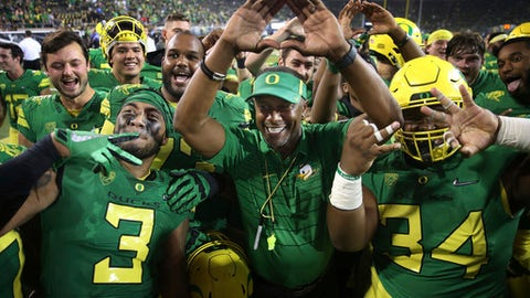 """Oregon coach Willie Taggart, center, throws the """"O"""" to fans as he celebrates with his team after a 77-21 victory over Southern Utah in an NCAA college football game Saturday, Sept. 2, 2017, in Eugene, Ore. (AP Photo/Chris Pietsch)"""