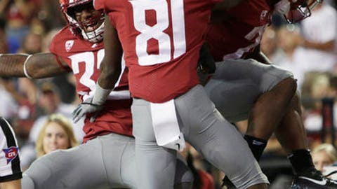 After scoring a touchdown, Washington State running back Jamal Morrow, right, celebrates with teammates wide receiver Renard Bell (81) and running back James Williams (32) during the second half of an NCAA college football game against Montana State in Pullman, Wash., Saturday, Sept. 2, 2017. Washington State won 31-0. (AP Photo/Young Kwak)
