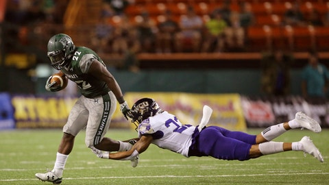 Western Carolina defensive back JerMichael White (22) trips up Hawaii running back Diocemy Saint Juste (22) during the third quarter of the NCAA college football game, Saturday, Sept. 2, 2017, in Honolulu. (AP Photo/Marco Garcia)