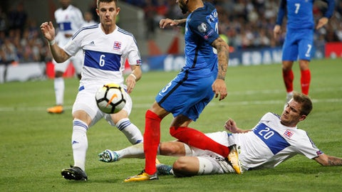 France's Layvin Kurzawa, center, challenges for the ball with Luxembourg's Chris Phillipps, left, and Luxembourg's David Turpel during the World Cup Group A qualifying soccer match between France and Luxembourg at the Stadium municipal in Toulouse, France, Sunday, Sept. 3, 2017. (AP Photo/Claude Paris)