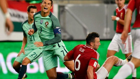 Hungary;s Akos Elek right, collides with Portugal's Cristiano Ronaldo, during the World Cup Group B first round soccer match between Hungary and Portugal, at the Groupama Arena, in Budapest, Hungary, Sunday, Sept. 3, 2017. (Tibor Illyes/MTI via AP)