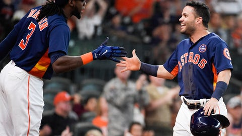 Houston Astros' Jose Altuve, right, celebrates scoring a run on Josh Reddick's sacrifice with Cameron Maybin during the seventh inning of a baseball game against the New York Mets, Sunday, Sept. 3, 2017, in Houston. (AP Photo/Eric Christian Smith)
