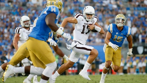 Texas A&M quarterback Nick Starkel, center, runs the ball against UCLA linebacker Krys Barnes, left, and defensive lineman Jaelan Phillips, right, during the second half of an NCAA college football game, Sunday, Sept. 3, 2017, in Pasadena, Calif. (AP Photo/Danny Moloshok)