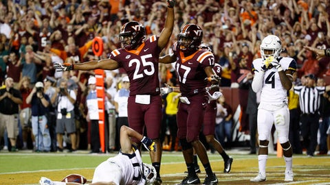 Virginia Tech linebacker Anthony Shegog (25) and safety Divino Deablo (17) celebrate after West Virginia wide receiver David Sills V, bottom, was unable to make a catch in the end zone in the final moments of an NCAA college football game in Landover, Md., Sunday, Sept. 3, 2017. Virginia Tech won 31-24. (AP Photo/Patrick Semansky)