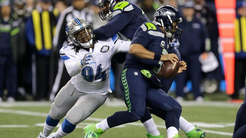 FILE - In this Jan. 7, 2017, file photo, Seattle Seahawks quarterback Russell Wilson, right, is pursued by Detroit Lions defensive end Ezekiel Ansah (94) as Ansah is blocked by Seattle Seahawks offensive tackle George Fant, center, in the first half of an NFL football NFC wild card playoff game, in Seattle. The Lions open their season on Sept. 10 against the Arizona Cardinals. (AP Photo/Stephen Brashear, File)