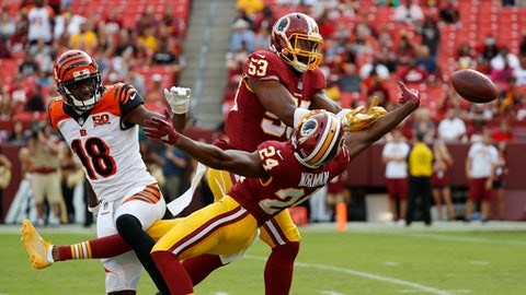 FILE - In this Aug. 27, 2017, file photo, Washington Redskins linebacker Zach Brown (53) and cornerback Josh Norman (24) break up a pass attempt to Cincinnati Bengals wide receiver A.J. Green (18) during a preseason NFL football game in Landover, Md. Defensive coordinator Greg Manusky's more aggressive defense should allow Norman, an All-Pro cornerback in 2015 with Carolina, to make more big plays. (AP Photo/Alex Brandon, File)