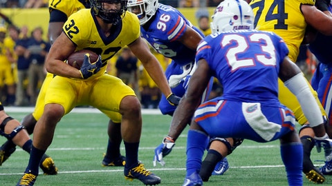 In this Sept. 2, 2017, photo, Michigan running back Ty Isaac (32) looks for running room as Florida defensive back Chauncey Gardner Jr. (23) defends in the first half of an NCAA college football game, in Arlington, Texas.  Isaac had a breakout performance with 114 yards rushing in the season-opening win over Florida. Wolverines coach Jim Harbaugh hopes the best is yet to come from the senior running back, whose career began at USC. (AP Photo/Tony Gutierrez, File)