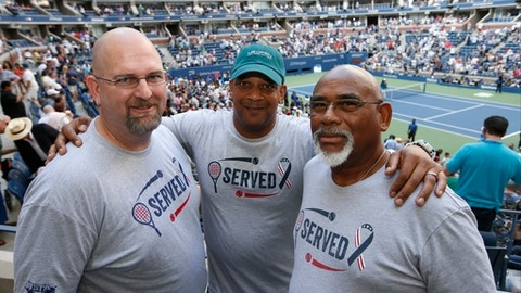 From left, military veterans Marc Spittler, Jon Atkins, and Henry Pruitt, all from Orlando, Fla., pose for a photo during a break in play during the fourth round of the U.S. Open tennis tournament, Monday, Sept. 4, 2017, in New York. (AP Photo/Jason Decrow)