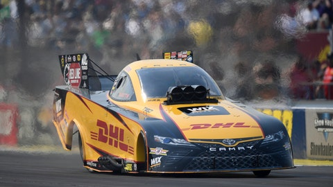 In this photo provided by the NHRA, J.R. Todd powers past Funny Car reigning world champion Ron Capps in his Dodge Charger in Indianapolis, Monday, Sept. 4, 2017. It is Todds first career win at the U.S. Nationals, his second of the season and of his Funny Car Career. (Jerry Foss/NHRA via AP)