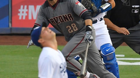 Arizona Diamondbacks' J.D. Martinez, second from left, runs to first as he hits a two-run home run as Los Angeles Dodgers starting pitcher Rich Hill, left, watches along with catcher Austin Barnes, second from right, and home plate umpire Alfonso Marquez run during the fourth inning of a baseball game, Monday, Sept. 4, 2017, in Los Angeles. (AP Photo/Mark J. Terrill)