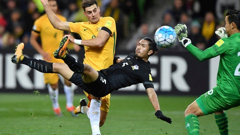 Australia's Tomi Juric, left attempts goal against Thailand's Adisorn Promrak, center, and Sinthaweechai Hathairattanakool, right, and during their World Cup Group B qualifying soccer match in Melbourne, Australia, Tuesday, Sept. 05, 2017. (AP Photo/Andy Brownbill)