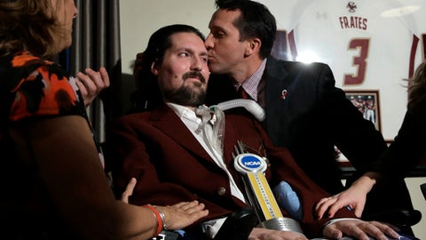 FILE - In this Dec. 13, 2016, file photo, former Boston College baseball captain Pete Frates, center left, receives a kiss from Boston College head baseball coach Mike Gambino after Frates was presented with the 2017 NCAA Inspiration Award, during ceremonies in Frates home in Beverly, Mass. The man who inspired the ice bucket challenge that has raised millions for ALS research is being honored at Boston City Hall. Mayor Martin Walsh is hosting a rally Tuesday, Sept. 5, 2017, for Frates at City Hall Plaza. The event coincides with the release of a new book on Frates. (AP Photo/Steven Senne, File)