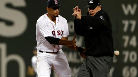 The ball hits umpire Jerry Layne as Boston Red Sox shortstop Xander Bogaerts tries to get a throw from the outfield on a double by Toronto Blue Jays' Jose Bautista during the fourth inning of a baseball game at Fenway Park in Boston Tuesday, Sept. 5, 2017. (AP Photo/Winslow Townson)