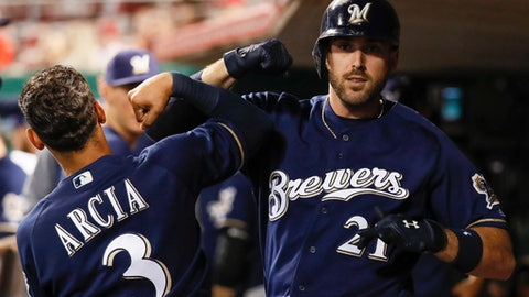 Milwaukee Brewers' Travis Shaw (21) celebrates in the dugout with Orlando Arcia (3) after hitting a two-run home run off Cincinnati Reds relief pitcher Ariel Hernandez during the eighth inning of a baseball game, Tuesday, Sept. 5, 2017, in Cincinnati. (AP Photo/John Minchillo)