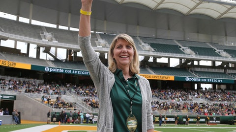"""FILE - In this April 22, 2017, file photo, Baylor's new president Linda A. Livingstone waves to the fans as she is introduced during the first half of the NCAA college football team's Green and Gold spring game, in Waco, Texas. Baylor University settled a federal lawsuit filed by a former student who said she was gang raped by two football players and alleged the program at the nation's largest Baptist school fostered a """"culture of violence."""" Details of the settlement announced Tuesday were not disclosed. The woman's attorney, John Clune, said the deal was reached within the last week. Clune credited new Baylor President Linda Livingstone with pushing Baylor to address the lawsuits and how it can improve its response to sexual assault in the future.  (Jerry Larson/Waco Tribune Herald via AP, File)"""