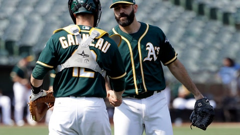 Oakland Athletics relief pitcher Chris Hatcher, right, shakes hands with catcher Dustin Garneau after the Athletics defeated the Los Angeles Angels 3-1 in a baseball game Wednesday, Sept. 6, 2017, in Oakland, Calif. (AP Photo/Marcio Jose Sanchez)