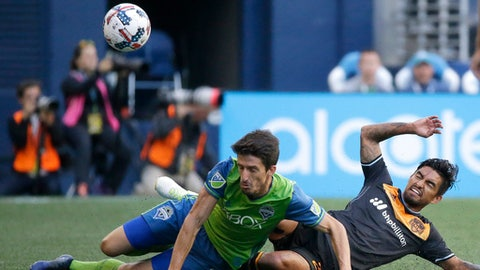 "FILE - In this June 4, 2017, file photo, Seattle Sounders midfielder Alvaro Fernandez, left, and Houston Dynamo defender A. J. DeLaGarza go down as they vied for the ball during an MLS soccer match in Seattle. DeLaGarza posted video of the floodwaters inching toward his home after Hurricane Harvey. ""Another sleepless night. Praying for those already in floods and hoping this rain stops. Much love H-Town,"" DeLaGarza wrote. (AP Photo/Ted S. Warren, File)"