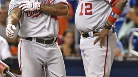 Washington Nationals' Howie Kendrick shows manager Dusty Baker were he got hit by pitch during the sixth inning of a baseball game against the Miami Marlins, Wednesday, Sept. 6, 2017, in Miami. (AP Photo/Gaston De Cardenas)