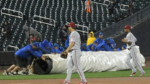 Philadelphia Phillies left fielder Hyun Soo Kim (31) and right fielder Nick Williams (5) walk off the field as the grounds crew rolls out the tarp for a rain delay during the sixth inning of the Phillies' baseball game against the New York Mets on Wednesday, Sept. 6, 2017, in New York. (AP Photo/Bill Kostroun)