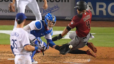 Arizona Diamondbacks' Ketel Marte, right, scores on a double by Adam Rosales as Los Angeles Dodgers catcher Yasmani Grandal takes a late throw and first baseman Cody Bellinger watches during the seventh inning of a baseball game, Wednesday, Sept. 6, 2017, in Los Angeles. (AP Photo/Mark J. Terrill)