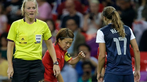 FILE- In this Thursday, Aug. 9, 2012 file photo, referee Bibiana Steinhaus from Germany, left, speaks to a Japanese player during the women's soccer gold medal match of the at the 2012 Summer Olympics in London. Steinhaus will make history in Germany on Sunday, Sept. 10, 2017, when she becomes the first woman to referee a Bundesliga game. (AP Photo/Julie Jacobson, File)