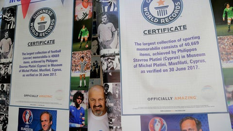 Philippos Stavrou Platini, owner of a museum poses for a photo by posters of French former soccer great and former UEFA president Michel Platini and two certificates of Guinness world records at his museum in Mosfiloti village, in the island of Cyprus, Friday, Sept. 8, 2017. A Cypriot man who idolizes Platini has managed clinched two entries in the latest annual Guinness Book of World Records book for his stash of photos, jerseys, shoes, balls and more centered on him. (AP Photo/Petros Karadjias)