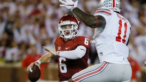 FILE - In this Sept. 17, 2016, file photo, Oklahoma quarterback Baker Mayfield (6) is pressured by Ohio State defensive end Jalyn Holmes (11) during an NCAA college football game in Norman, Okla. Mayfield clearly recalls the nightmare that transpired in Norman last year when Ohio State came to town a year ago.  (AP Photo/Sue Ogrocki, File)