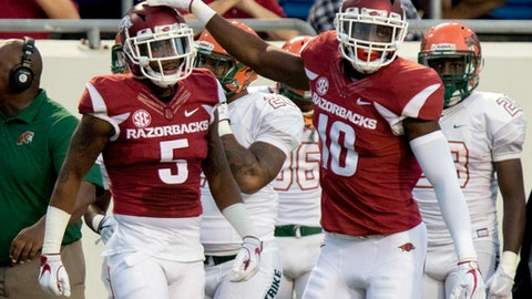 FILE - In this Aug. 31, 2017, file photo, Arkansas defensive back Henre' Toliver (5) and linebacker Randy Ramsey (10) celebrate after a broken-up pass during the second quarter of an NCAA college football game against Florida A&M in Little Rock, Ark. After a convincing season-opening win over Florida A&M, Arkansas makes a step up in competition when it hosts No. 23 TCU on Saturday, Sept. 9, 2017. (AP Photo/Gareth Patterson, File)