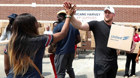 FILE - In this Sept. 3, 2017, file photo, Anna Ucheomumu, left, high fives Houston Texans defensive end J.J. Watt after loading a car with relief supplies to people impacted by Hurricane Harvey, in Houston. J.J. Watt is being honored by the NFL Players Association after raising more than $29 million for Hurricane Harvey relief efforts. Watt was named the NFLPA's Community MVP on Friday, Sept. 8, 2017,  for his work in the days since the hurricane and flooding devastated Houston and much of southeast Texas. (Brett Coomer/Houston Chronicle via AP, Pool, File)